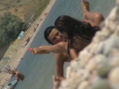 Two hot chicks flexing their bodies, spreading legs and posing be advantageous to a camera held by their girl friend. Sexy poses of their lean tanned bodies are also caught on a spy beach cam video.